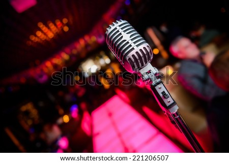 Retro microphone against colourful background - stock photo