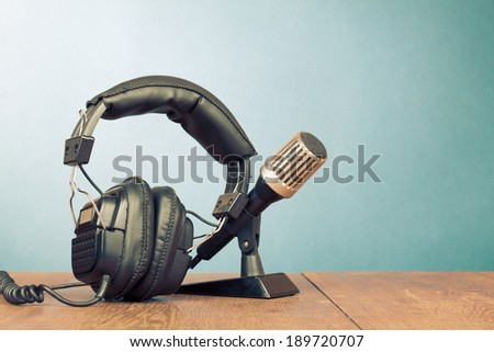 Retro microphone and headphones on table - stock photo