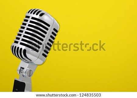 Retro microphone isolated on yellow background - stock photo