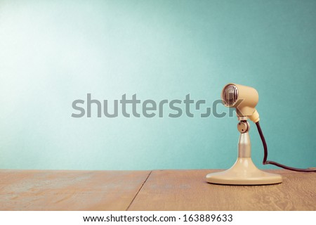 Retro microphone on table in front mint green background - stock photo