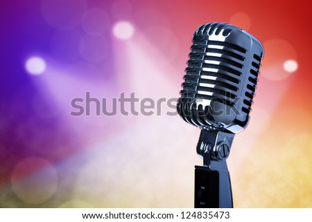 Retro microphone with stage lighting background - stock photo