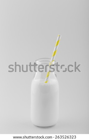 Retro Milk Bottle with a Yellow Striped Drinking Straw. Selective Color.  - stock photo