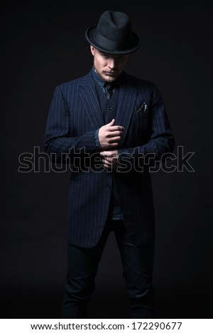 Retro 1900 modern fashion man with blonde hair and beard. Wearing blue striped suit and black hat. Studio shot against black. - stock photo