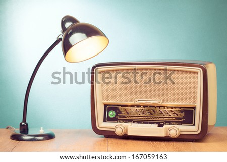 Retro old desk lamp and radio on table - stock photo