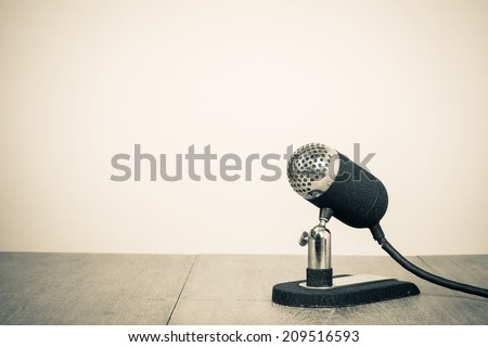 Retro old microphone on table sepia photo - stock photo