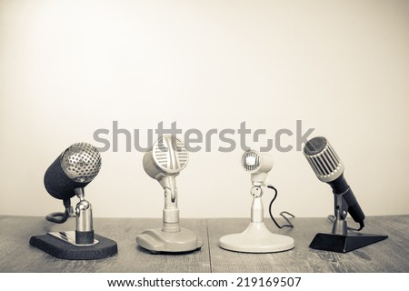 Retro old microphones on table. Vintage style sepia photo - stock photo