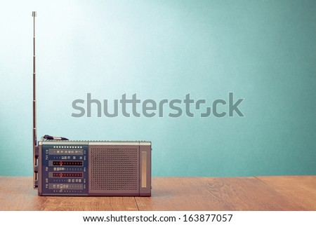 Retro old radio receiver on table front  mint green background - stock photo