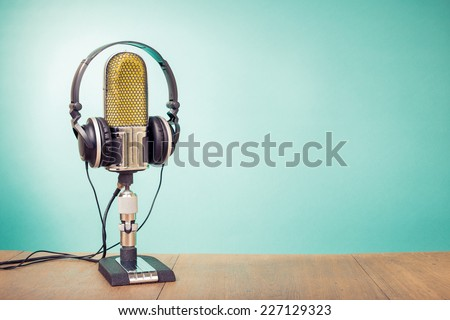 Retro old ribbon microphone and headphones front mint green background - stock photo