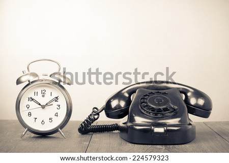 Retro old rotary telephone and alarm clock on table. Vintage style sepia photography - stock photo