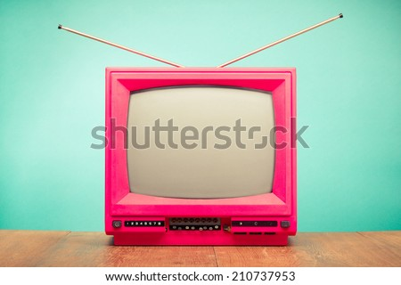 Retro old television with antenna on table front mint green background - stock photo