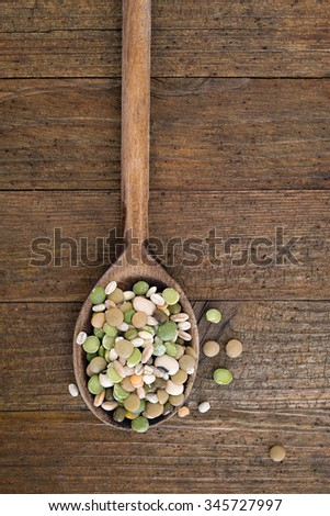 Retro old wooden spoon on wooden background with soup ingredients including split peas, red lentils, pearl barley, spelt and black eyed peas. Well used kitchen utensil.  - stock photo