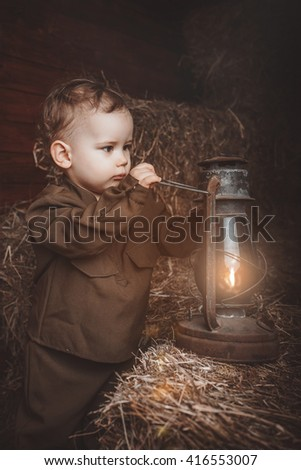 Retro! One year baby in Second World War russian uniform. With lamp. Hay background - stock photo