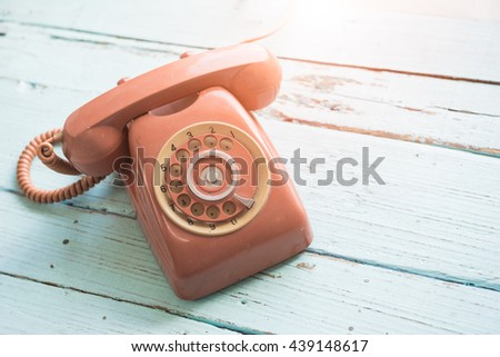 Retro orange-red telephone on the old wooden table. - stock photo