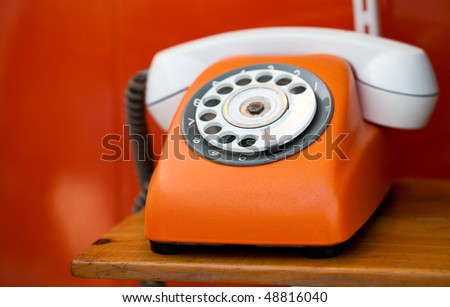 Retro orange telephone on red background - stock photo