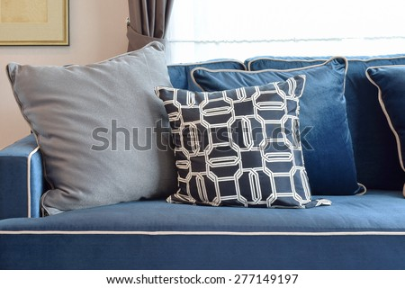 Retro pattern, gray and blue pillow setting up on navy blue classic sofa - stock photo