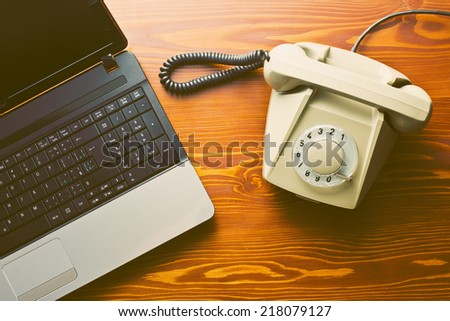 retro phone and modern laptop on wooden table - stock photo
