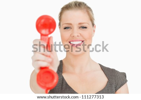 Retro phone red in a hand of a pretty woman against white background - stock photo
