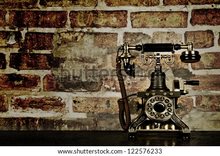 Retro Phone - Vintage Telephone on Old Desk with Brick Wall - stock photo