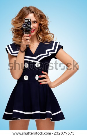 Retro photo of a glamorous pin-up sailor girl with an old vintage cinema 8 mm camera, looking like a sexy producer, shooting a movie on blue background. - stock photo