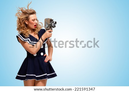 Retro photo of a glamorous pin-up sailor girl with an old vintage cinema 8 mm camera shooting a movie on blue background. - stock photo