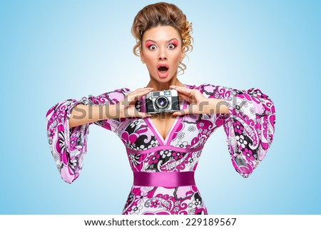 Retro photo of an amazed fashionable hippie homemaker, holding an old vintage photo camera with two hands and showing emotions on blue background. - stock photo