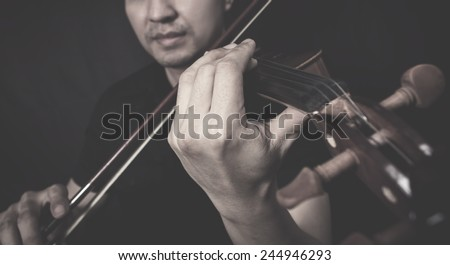 retro photo of asian handsome violinist musician plays old vintage classical violin on dark background , focus to left hand  - stock photo