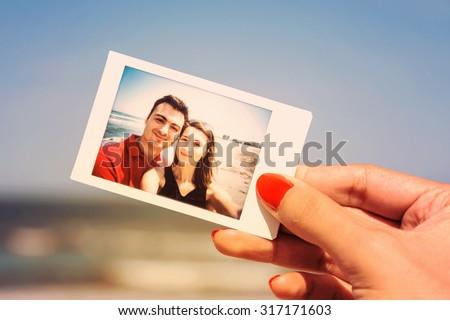 Retro Photo Of Girl Hand Holding Instant Photo Of Happy Couple On Beach - stock photo