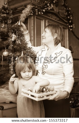 Retro photo of grandmother and baby girl decorating Christmas tree at  home - stock photo