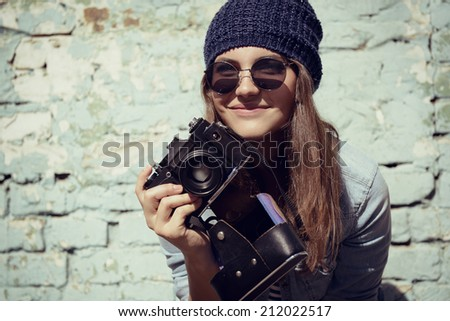 Retro photographer. Modern urban girl has fun with vintage photo camera outdoor near grunge wall, image toned. - stock photo