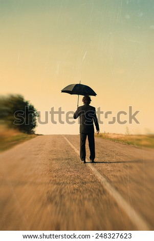 Retro picture of rear view of man with umbrella on the road - stock photo