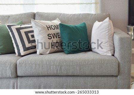 Retro pillows on the cozy grey sofa in the living room - stock photo