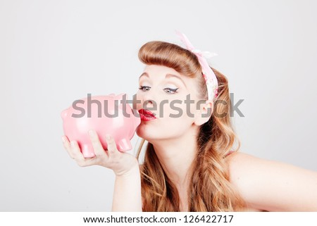 retro pinup woman with piggy bank as saving or spending concept - stock photo