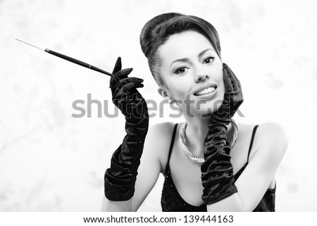 Retro portrait of a beautiful woman in great cocktail dress smoking a cigarette with holder. Jewelry and Beauty. Vintage (Hollywood) style. Classic old movie star. Close-up. Copy-space. Studio shot - stock photo