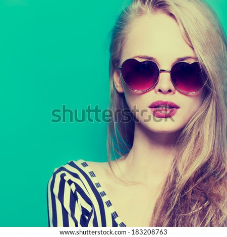retro portrait of a beautiful young woman wearing sunglasses - stock photo