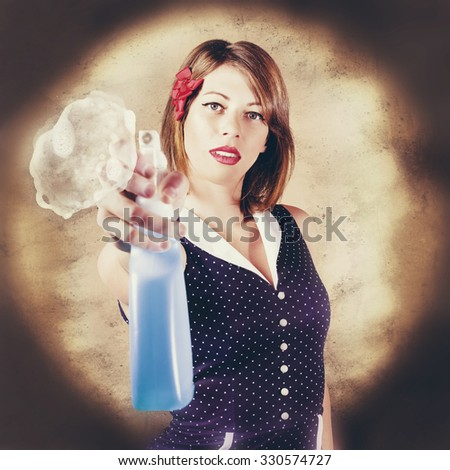 Retro portrait of a trigger happy housewife shooting blue antiseptic spray bottle on glass surface when house cleaning. Pump action pin up - stock photo