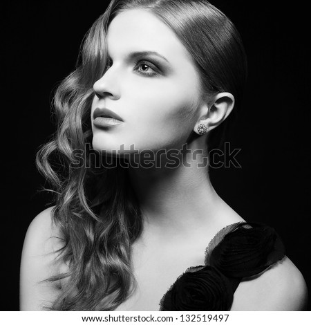 Retro portrait of inaccessible beautiful woman in black dress with smoky eyes and diamond earring. Femme fatale in film noir. Vintage (Hollywood) style. Black & white studio shot - stock photo