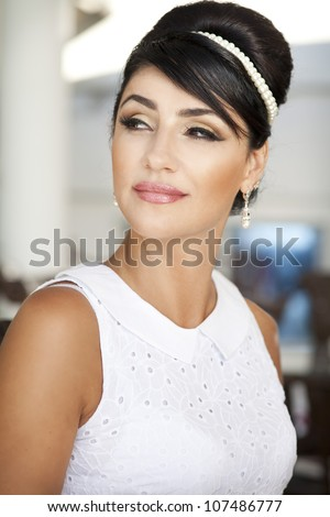 retro portrait of vintage beautiful woman at apartment.Retro style. Stylish rich slim girl in white dress and makeup with glossy hair. glamorous alluring lady at vacation at luxury villa.France.series - stock photo