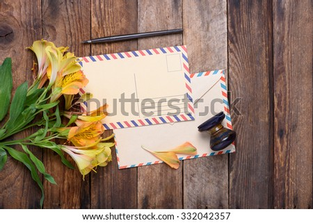 Retro postcard with envelope, stamp and flowers on vintage wooden table still life - stock photo
