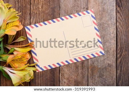 Retro postcard with flowers on vintage wooden table - stock photo