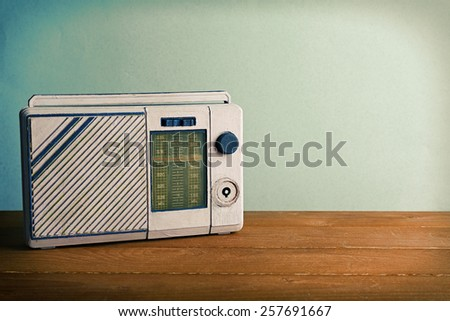 Retro radio on wooden table on light colorful background - stock photo