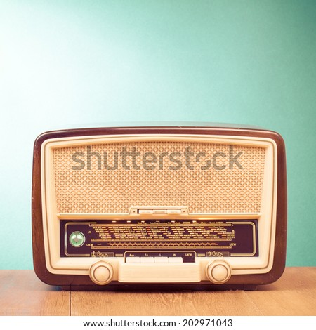 Retro radio receiver on table front mint green background - stock photo