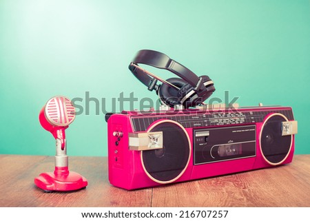 Retro radio recorder, microphone and headphones front mint green background - stock photo