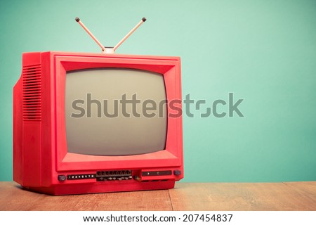 Retro red old television front mint green background - stock photo