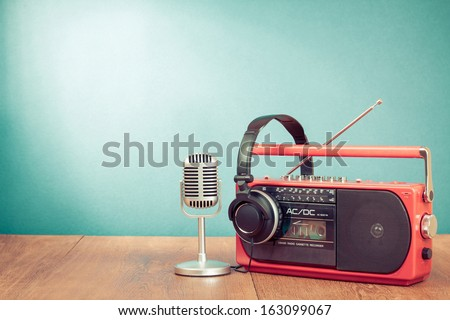 Retro red radio cassette player, headphones, microphone on table - stock photo