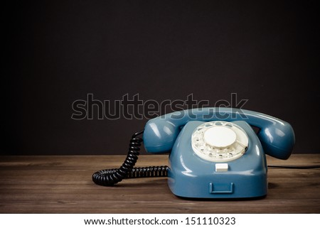 Retro rotary telephone on table against black background - stock photo