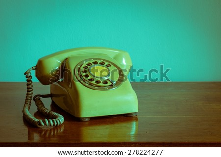 Retro rotary telephone on wood table - stock photo