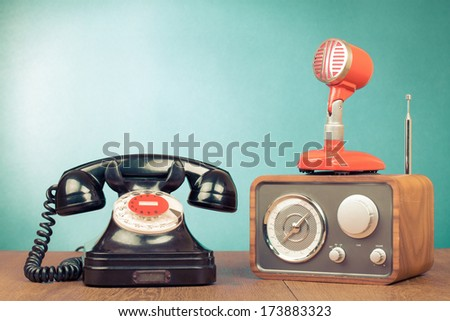Retro rotary telephone, radio, microphone on table - stock photo