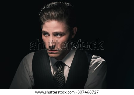 Retro 1940s fashion man in waistcoast and tie. Grease hair combed back. Against dark background. - stock photo