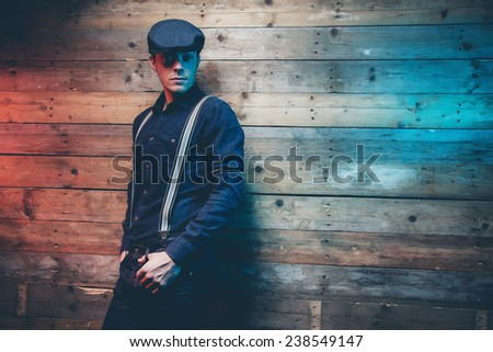 Retro 30s fashion man wearing blue cap, shirt, braces and jeans trousers. Leaning against old wooden wall. - stock photo