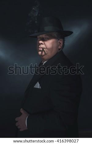 Retro 1930s gangster smoking cigar. Classic studio portrait. - stock photo